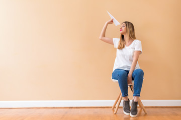 Young woman with a paper airplane in a chair