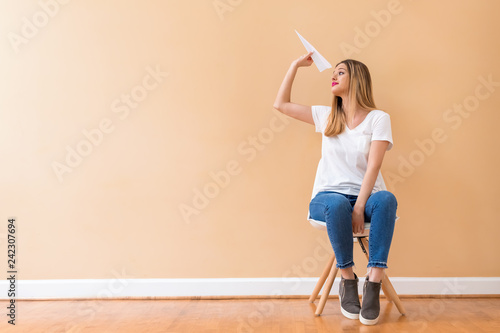 Foto Murales Young woman with a paper airplane in a chair