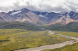 Dry River Bed Running Through Valley Between Mountains In Alaska