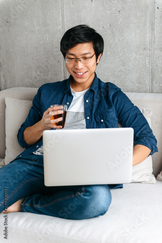 Happy asian man sitting on a couch at home, looking