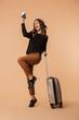 Leinwandbild Motiv Amazing young woman posing isolated holding passport with tickets and suitcase.