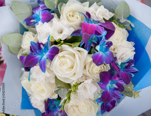 Bouquet of white roses and blue orchids.
