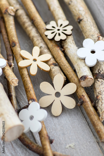Group of light brown and white wooden flowers on gray birch branches on wooden table - 242314633