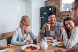 Group of multiethnic friends eating pancakes and having fun at home. - 242315216