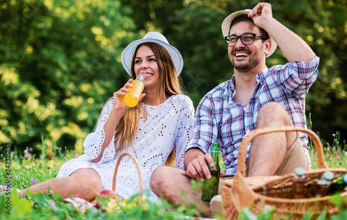 Leinwanddruck Bild Loving couple enjoying picnic in the park. Love and tenderness, dating, romance, lifestyle concept