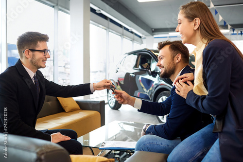 Couple buys a car in a car dealership - 242320218