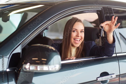 A female driver smiles and holds car keys.