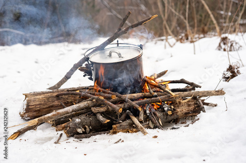 Winter hike: a small bonfire in the forest and a pot on the fire. - 242321629