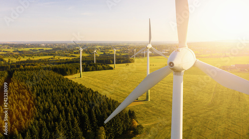Wind turbines and agricultural fields on a summer day - Energy Production with clean and Renewable Energy - aerial shot, analog image style