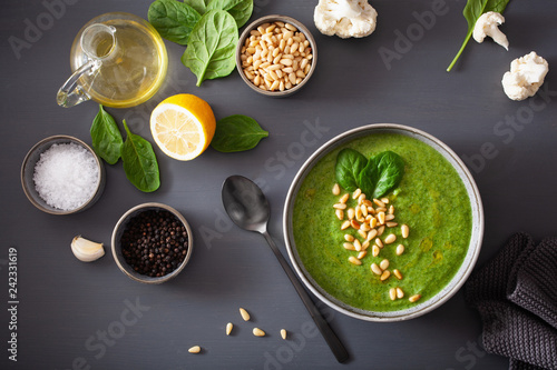 green creamy cauliflower spinach soup on gray background - 242331619