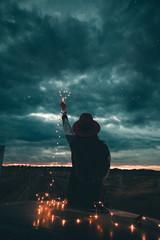 Ragazzo con il simbolo del cuore in mano rivolto verso il cielo nuvoloso fa un regalo per San Valentino