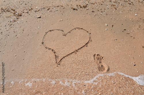 рисунок сердца и след девушки на пляже у моря