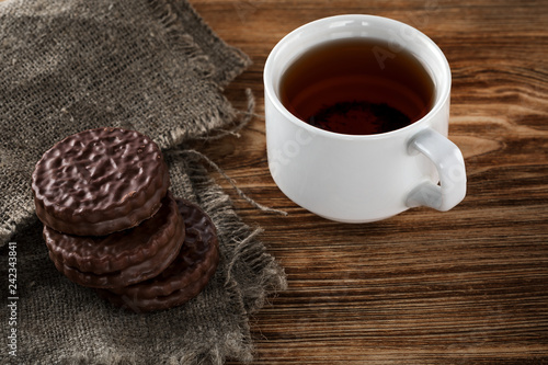 Chocolate chip cookies and a mug of tea on a white wooden table.