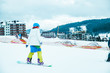 man in colored costume on snowboard. snowed mountains on background. winter vacation