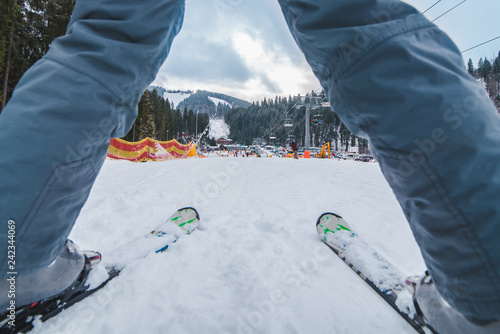 ski track close up view between legs. winter sport activity. frosty snowed weather