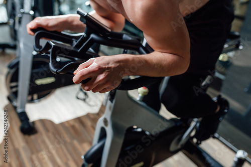 Close up mid section of fit young men working on exercise bikes at the gym