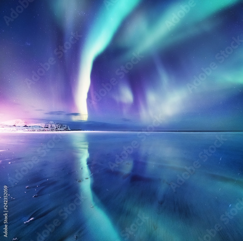 Foto Murales Aurora borealis on the Lofoten islands, Norway. Green northern lights above mountains. Night sky with polar lights. Night winter landscape with aurora and reflection on the water surface.