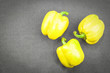 three yellow sweet pepper on dark textile background, top view