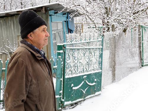 Leinwandbild Motiv Elderly man standing on the rural street near the shack and iron gates during a snowfall. Concept of cold weather, snow winter, homeless