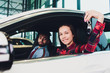 Photo of young smiling mixed race woman sitting inside her new car and holding key. Concept for car rental.