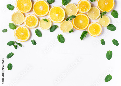 Photo of orange and lemon slices with mint on a white background. Background for the design of banners, websites, blogs, information block. Frame for banner with orange and lemon - 242374296