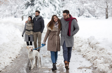 Couple walking dog in park on snow