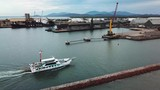 Drone moving foward showing vehicle barge cruising into harbour. Industrial port facilities can be seen in background. Location Townsville, Australia. - 242382653