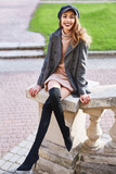 beautiful fashionable stylish woman in gray coat and black knee high heel boots walking and posing outdoors, , street style shooting - 242390457
