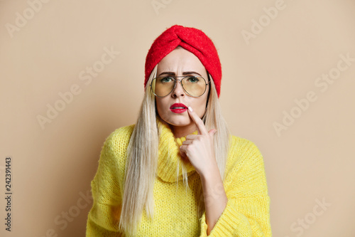 Leinwanddruck Bild Beautiful young woman pointing finger to her lips contouring applying balm to starting herpes virus