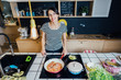 Leinwandbild Motiv Smiling woman cooking a healthy meal in home kitchen.Making dinner on kitchen island.Preparing chicken,enjoying spice aromas.Eating in.Passion for cooking.Healthy lifestyle and dieting concept.
