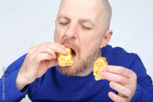 Foto Murales bearded man in a blue sweater eating a honeycomb