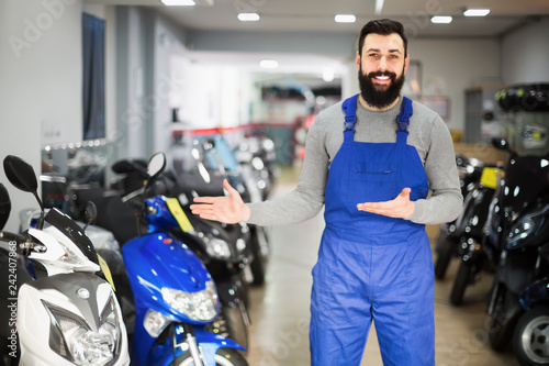 Worker demonstrating motorcycles  in workplace