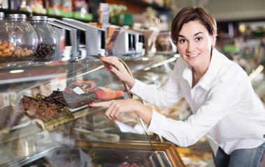 Adult female client choosing delicious dessert