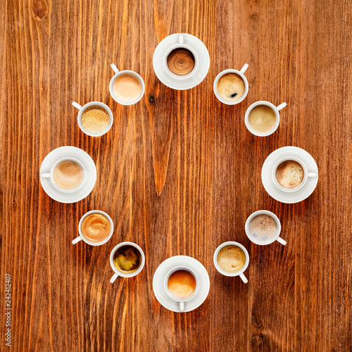 Some cups of coffee on wooden table, top view. Coffee brake concept.
