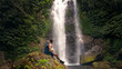 man sitting on a stone overlooking the waterfall Bali Indonesia - 242417401