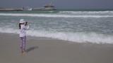 Teenage girl shoots on smartphone the sea waves on Public Jumeirah Open Beach on the coast of the Persian Gulf, Dubai