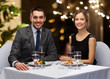 Leinwanddruck Bild - people and leisure concept - smiling couple with food and non-alcoholic red wine at restaurant over festive lights on background