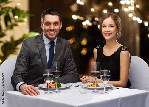 Leinwandbild Motiv people and leisure concept - smiling couple with food and non-alcoholic red wine at restaurant over festive lights on background
