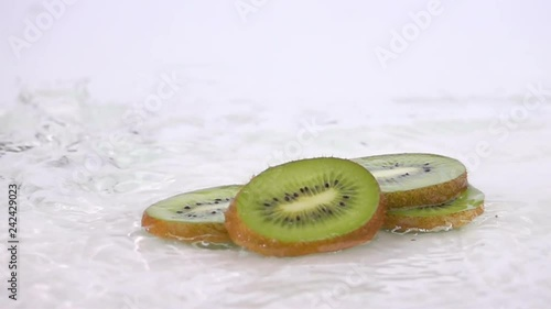 a several slices of kiwi are falling on the table