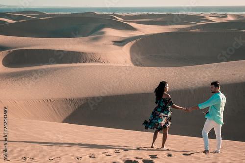 couple walking during sunset in the desert sand dunes of Maspalomas Gran Canaria, Maspalomas desert beach Gran Canary