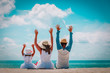 happy family with child hands up on beach