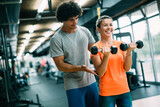 Personal trainer giving instructions in modern gym - 242437484
