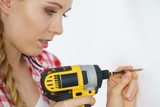Woman drilling in wall - 242447095