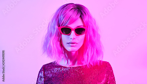 Sexy woman in party bright luxury outfit. High Fashion. Model girl with pink blonde dyed hair, makeup. Colorful neon light. Night Clubbing art style