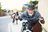 Active senior couple with electrobikes standing outdoors on a road in town. - 242452066