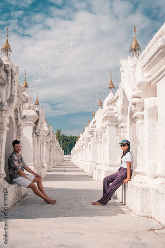 Kuthodaw pagoda in Mandalay, Burma Myanmar, happy young couple men and woman on vacation in Myanmar walking by white temple pagoda the largest book in the world
