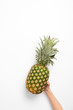 cropped view of woman holding organic pineapple in hand on white background