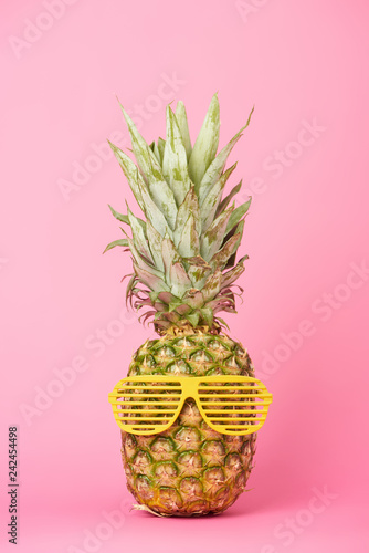 funny and tasty pineapple in sunglasses on pink background