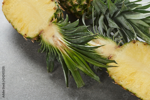 halves of ripe yellow pineapple on grey background