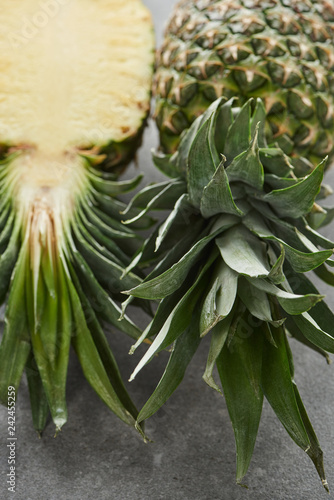 ripe half and whole pineapples on grey background